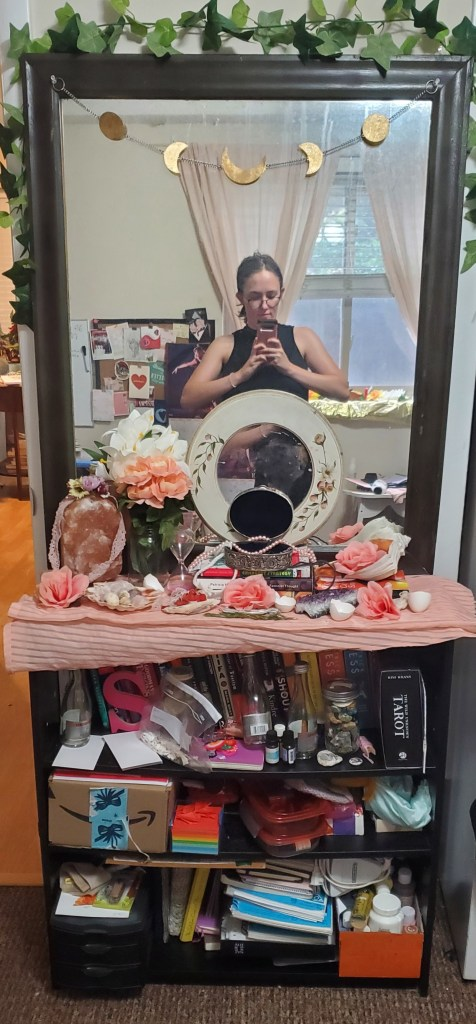 Photo of a small black bookshelf filled with items and a large mirror on tops