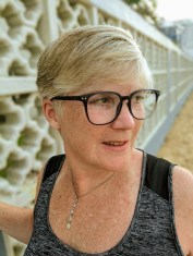 A light-skinned woman from the shoulders up with short blonde hair and glasses. She is wearing a black tank top and a necklace, and is looking off to the side.