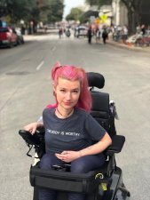 """A white woman in a power wheelchair sitting in the middle of an empty street. She has pink hair up in pigtails and is wearing a gray shirt with the words """"This Body is Worthy"""" across the front."""