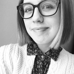 A headshot of Katy DeCoste in black and white. They are wearing black, square glasses, a floral-patterned collared shirt, and white cardigan. They are smiling and have short, light hair.