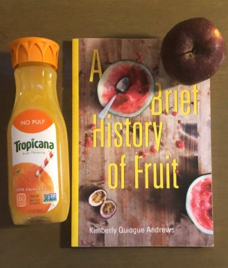 A book (A Brief History of Fruit by Kimberly Quiogue Andrews) on a desk with an apple and a small bottle of orange juice next to it.
