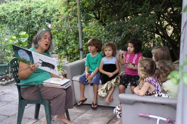 teacher reading a book to children
