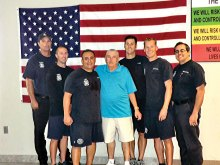 """Surrounding Mr. Marr in the blue shirt is the lifesaving crew (left to right) firefighter Tom Geffert, firefighter Ricky Quinn, paramedic Les Legarreta, firefighter Brent Kohl, engineer David DeGraaf and Captain Robert Olmstead. Mr. Marr said, """"These men are my heroes."""""""