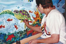 Bev Walter works on a mural at The Center Against Family Violence.