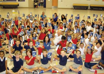 Rotarians Gary and Bonnie Whiting present dictionaries to third grade students at Navarette Elementary School.