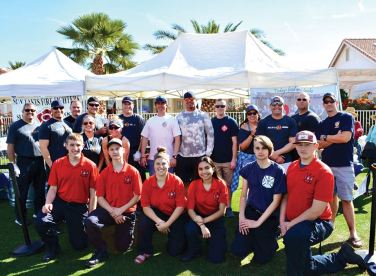 A delegation of Sun Lakes firefighters with a big assist from students (kneeling) from the Central Arizona Valley Institute of Technology cooked hot dogs and hamburgers for the crowd at the Art at the Lakes event. Photo by Brian Curry.
