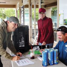Player Bill Cunningham checks in with tournament Director Josh Bates while Assistant Director John Radcliffe looks on.