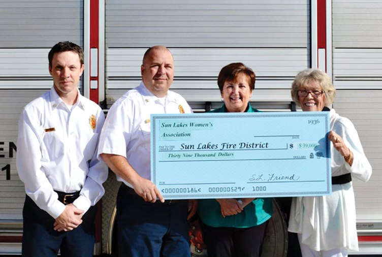 "Pictured (left to right): Sun Lakes Fire District Deputy Chief Rob Helie and Chief Troy Maloney are presented a ""check"" for $39,000 for the purchase of state-of-the-art emergency band radios by Sun Lakes Women's Association President Judy Caniglia and Vice President Marjorie Shipe."
