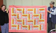 """Jeannie Sanders (left) and Sue Bart (right) display a """"Rail Fence"""" quilt."""