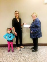 "Geri Hall from P.E.O. Chapter DD, Sun Lakes, presents PCE grant recipient Melissa Leffler (with daughter ""Izzy"") with the P.E.O International Grant Award for Continuing Education."