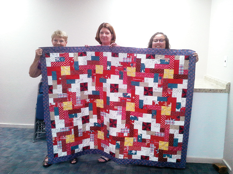 Betty Peer, Janice Cournoyer and Stephanie Reynolds of Post 8053 Auxiliary with an Arizona Quilt Crew quilt. The quilt was pieced and donated by Torrie Malone, a friend of the group, and quilted by Kay Rapp, a member of the group.