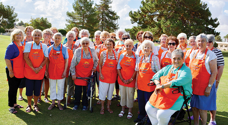 """The Sun Lakes Women's Association members getting ready for the Fall Bazaar in their """"striking"""" orange aprons"""