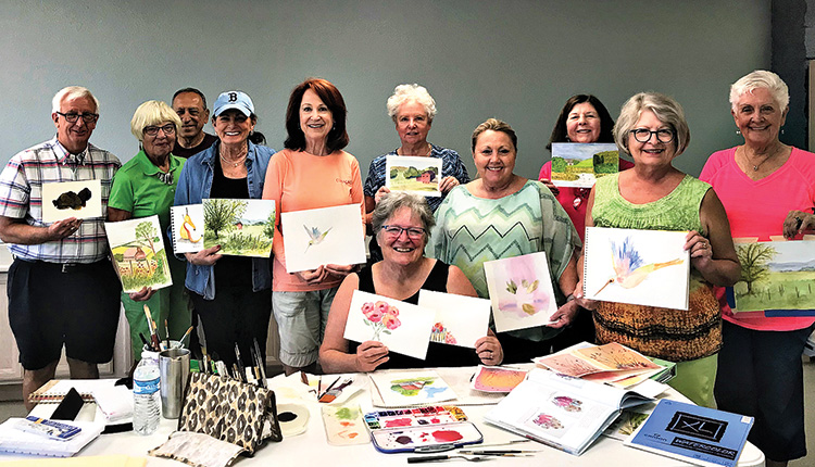 Jean Anderson (seated) with students in her beginning watercolor class displaying examples of their work