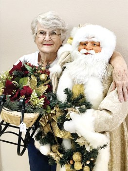 Phyllis Hesselrode of Sun Lakes, chairperson of the Holiday Happenings event for Assistance League of East Valley, shares a hug with a five-foot-tall Santa, which will be among the decorations for sale.