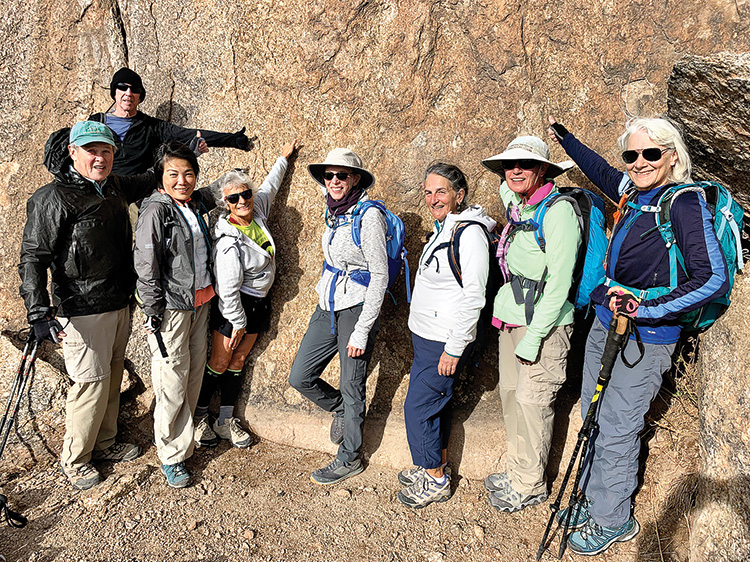 """Club hikers giving a """"Thumbs Up"""" at the top of Tom's Thumb. Pictured (left to right) are Brian Hill, Tim Allen, Mei-Mei Ahlskog, Dena Brinkman, Diane Alessi, Jeannette Chenier, DeEtte Faith, and Marilyn Harkins. (Photo by Warren Wasescha)"""