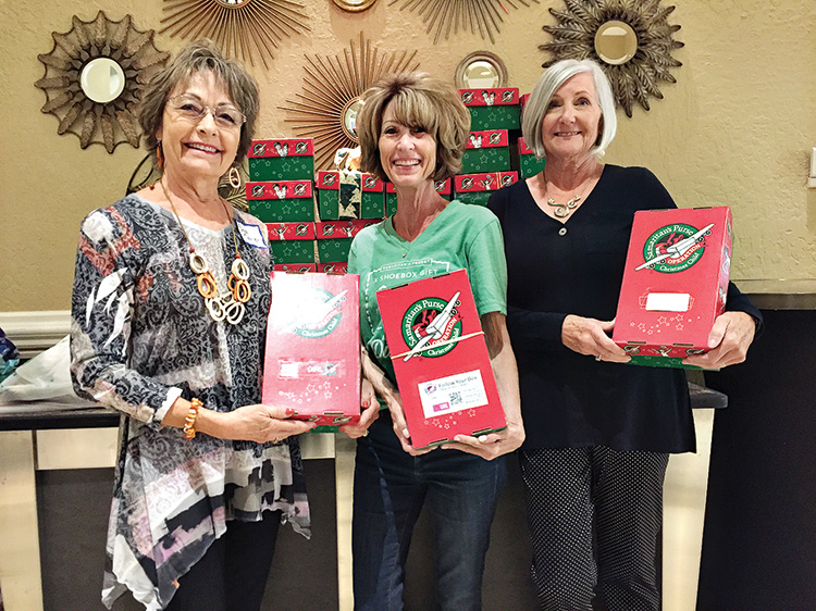 Sue Elsner, Connie Huisken of Operation Christmas Child, and Sue Reynhout with donated shoeboxes