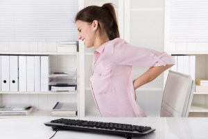 Woman in grimacing holding painful back