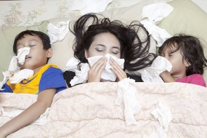 Mother and children with colds lying in bed blowing their noses.
