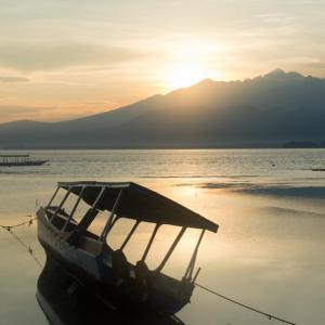 Sonnenaufgang mit Boot im Vordergrund auf Gili Air