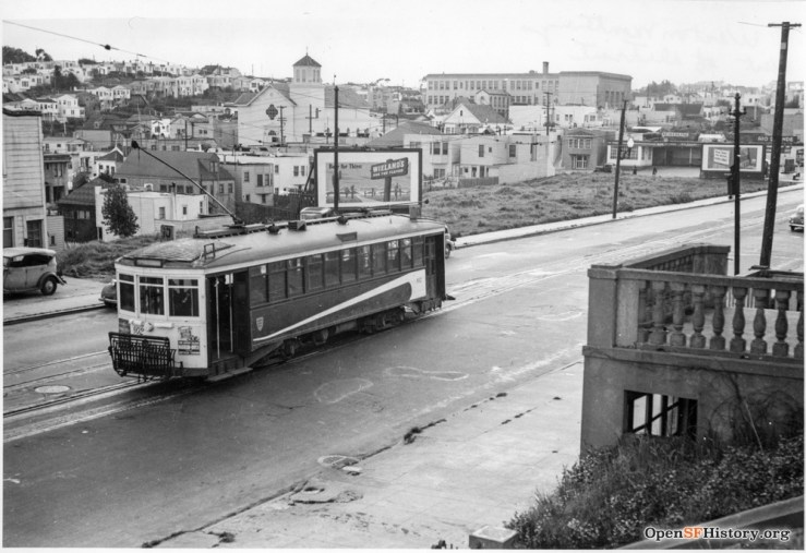 1940c. Monterey Blvd at Detroit. Top of Lower Detroit Steps is hidden behind streetcar. St Finn Barr Church and Sunnyside School visible in distance. Note billboards in middle distance. OpenSFHistory.org
