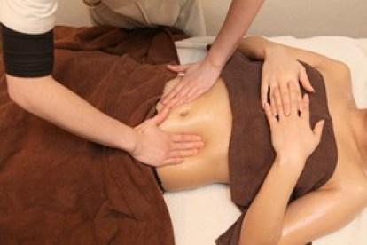 女性専用施術ルームでお腹のオイルマッージを受ける女性