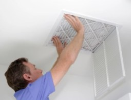 man replacing air filter in home– when to change my air filter - Fort Myers - Sunset Air Home and Home Services