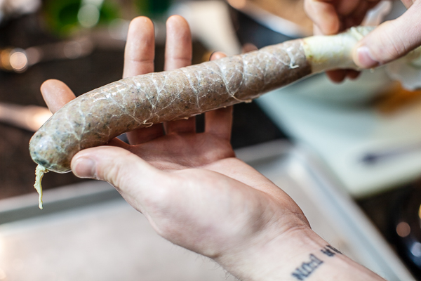 sausage being guided into casing from stuffer