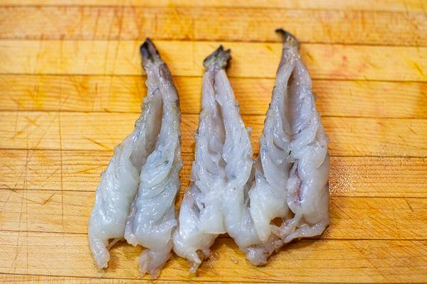 butterflied raw shrimp on cutting board