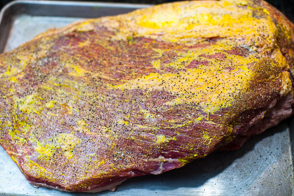 uncooked underside of brisket slathered with mustard and sprinkled with salt and pepper