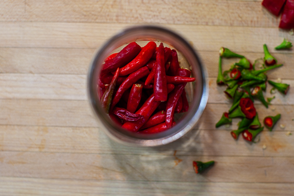 chile peppers with tops removed in a glass jar