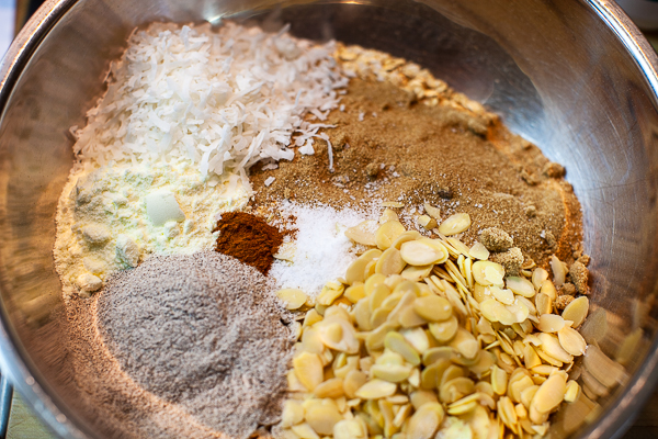 metal mixing bowl containing rolled oats, brown sugar, almonds, buckwheat, milk powder, salt, cinnamon, coconut flakes