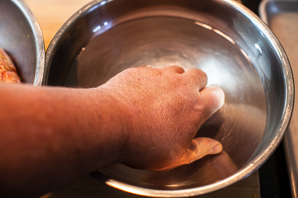 hand immersed in metal mixing bowl containing water