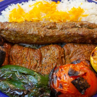 Platter of Koobideh, kabab, grilled pepper, tomato, lemon, eggplant, dill yogurt, saffron rice