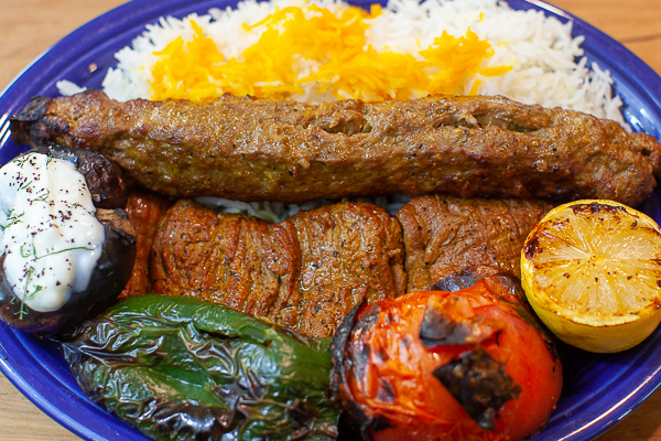 plate of Koobideh, Barb Kebab, rice, grilled pepper, tomato, lemon, eggplant, dill yogurt sauce