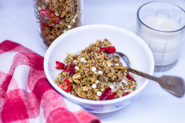 bowl of granola with spoon, next to red and white checkered napkin, jar of granola and small glass of milk.