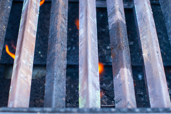 gas grill with grates removed, yellow flame