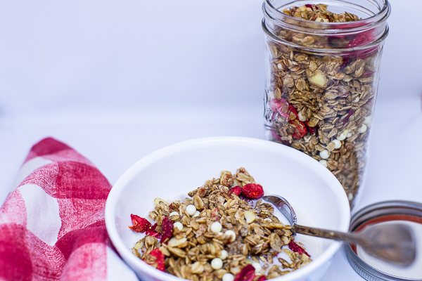 bowl containing granola and milk next to red and white checkered napkin and jar of granola
