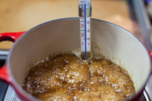 pot contining bubbling sugar and butter mixture wth candy thermometer hooked inside
