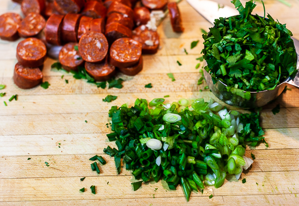 andouille sausage, cilantro, green onion (scallions) on wooden cutting board.