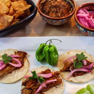A plate of conchinita pibil tacos with habanero salsa and pickled red onions.