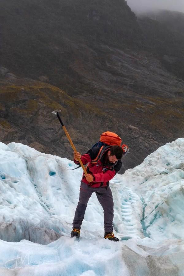 Гид прорубает ступеньки во льду во время хели-хайка по леднику Фокса