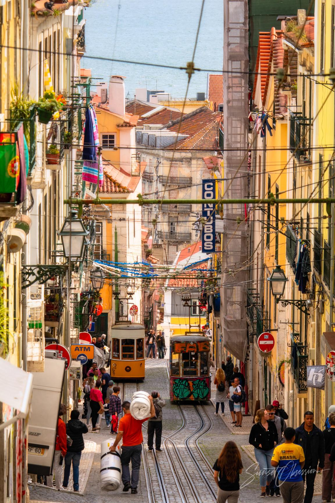 A view of the Bica lift street in Lisbon on a busy afternoon