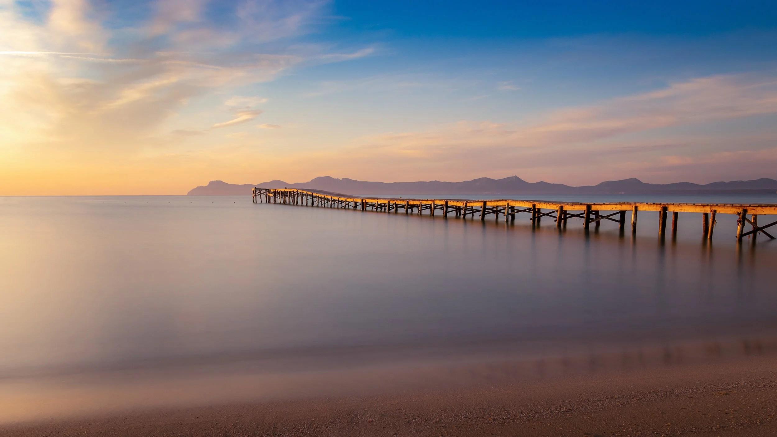 Один из деревянных пирсов пляжа Муро на рассвете