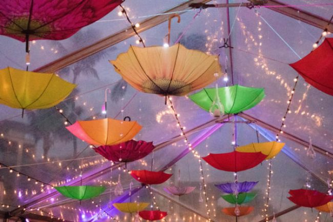 Clear tent in the rain strung with lights and colorful umbrellas