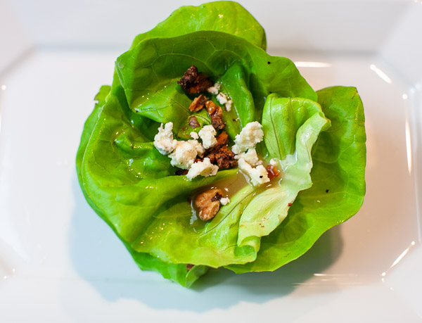 layering lettuce leaves and topping with walnuts, dressing and blue cheese