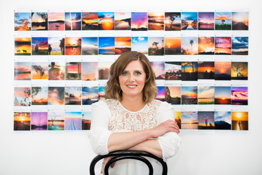 Kate sits on a chair in front of a wall covered in sunset photos
