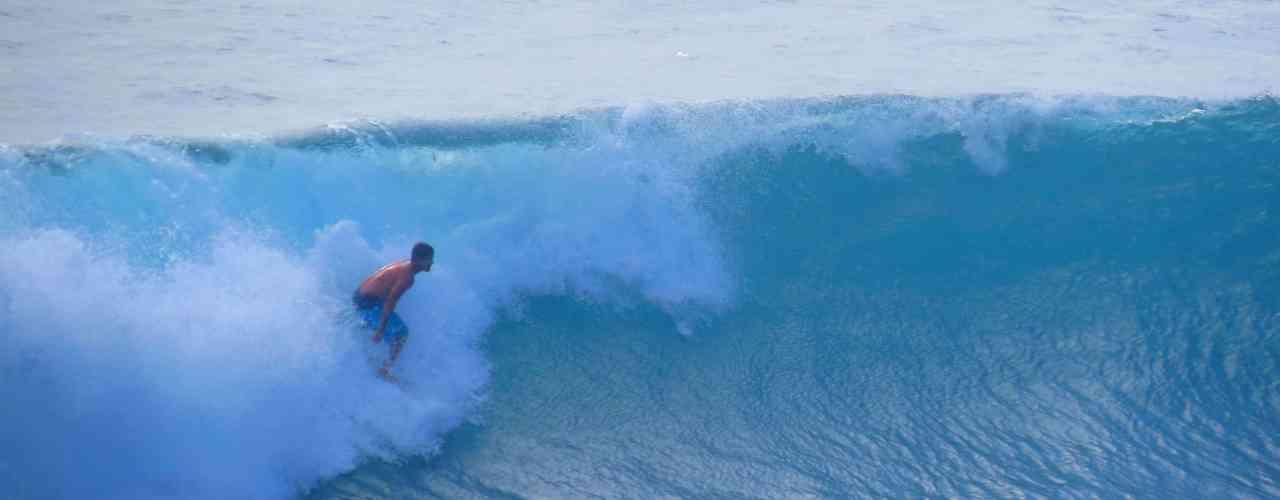 Surfer surfing in Uluwatu