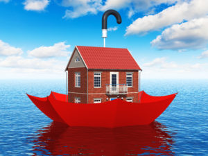 Creative real estate security, home protection and insurance business concept: residential house cottage floating in blue sea water ocean in red umbrella parasol
