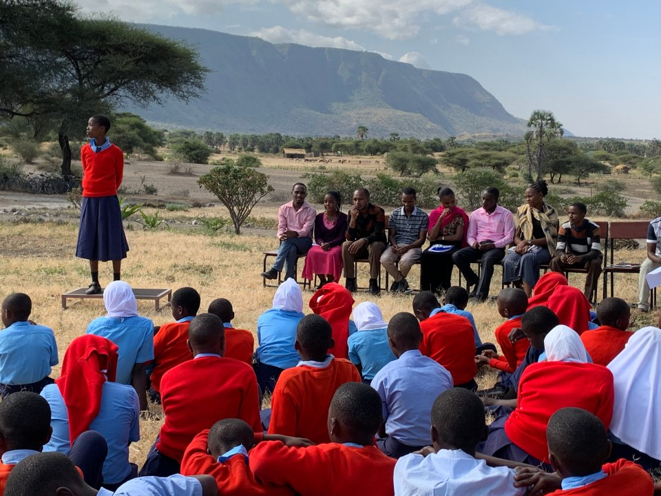 Student giving campaign speech for student body with Great Rift Valley escarpment in the background.