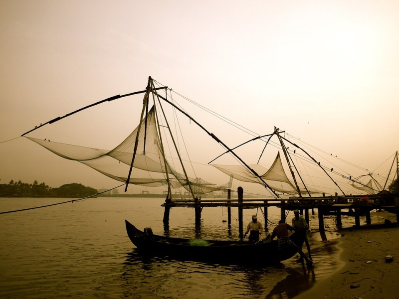 fishermen next to chinese fishing nets in kochi